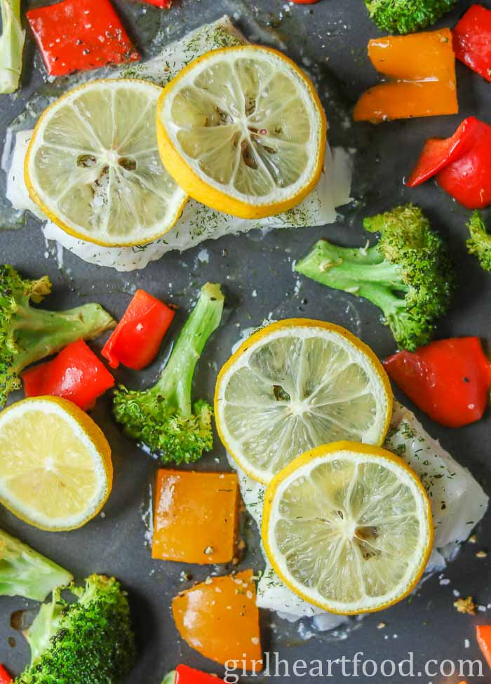 Sheet pan cod with lemon slices on a sheet pan with vegetables.