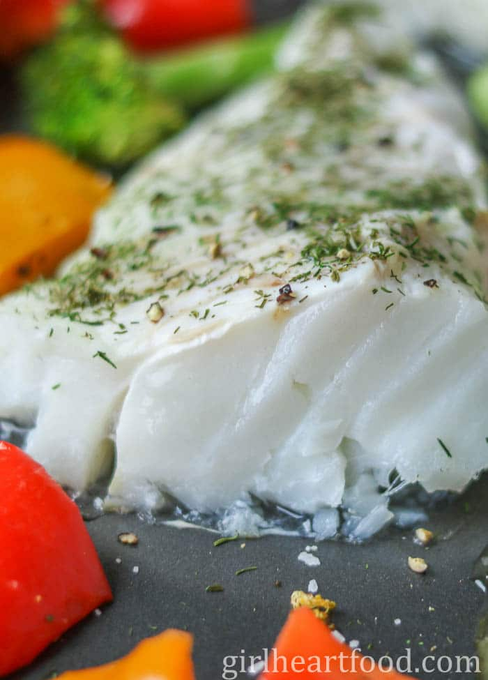 Close up of a piece of lemon baked cod with dill.