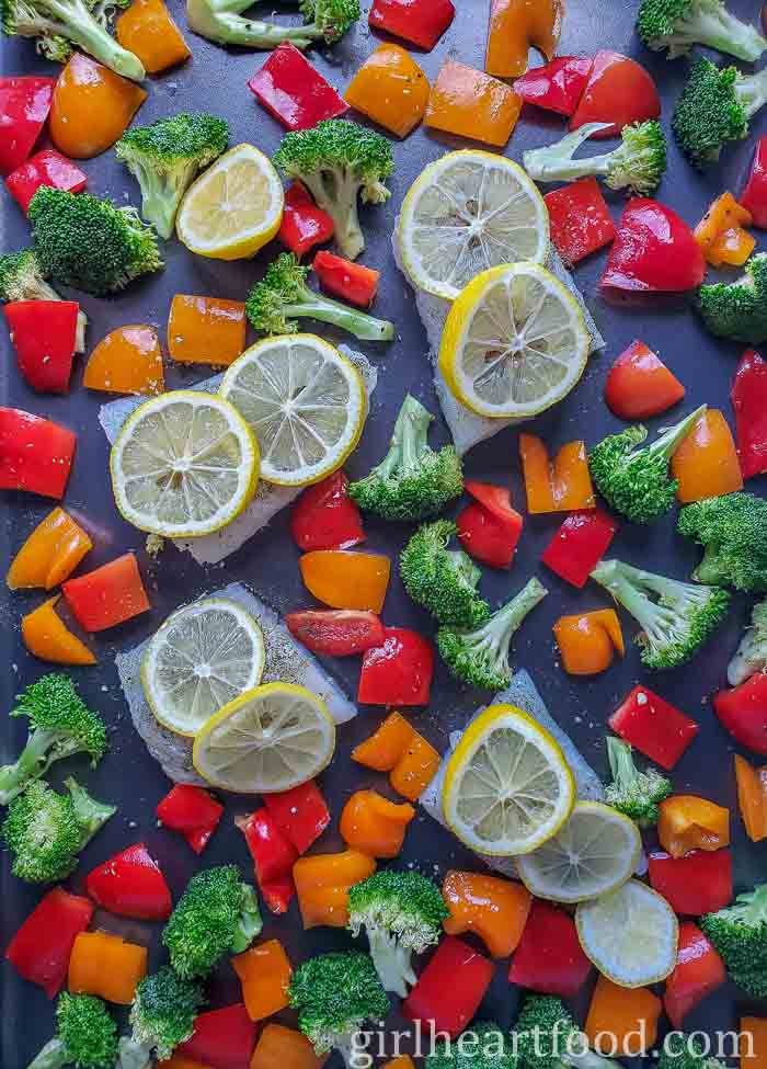 Cod fillets with lemon slices and vegetables on a sheet pan.