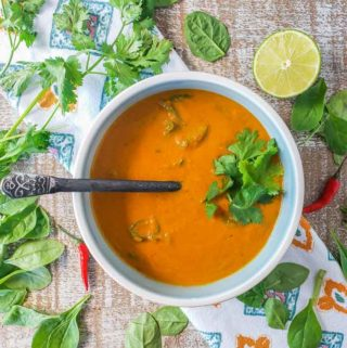 Bowl of curried pumpkin soup with coconut milk garnished with fresh cilantro and a spoon in the bowl.