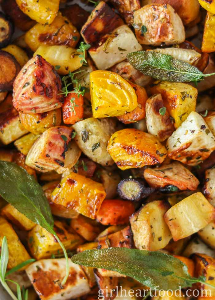 Close-up of a chunks of roasted root vegetables with herbs.