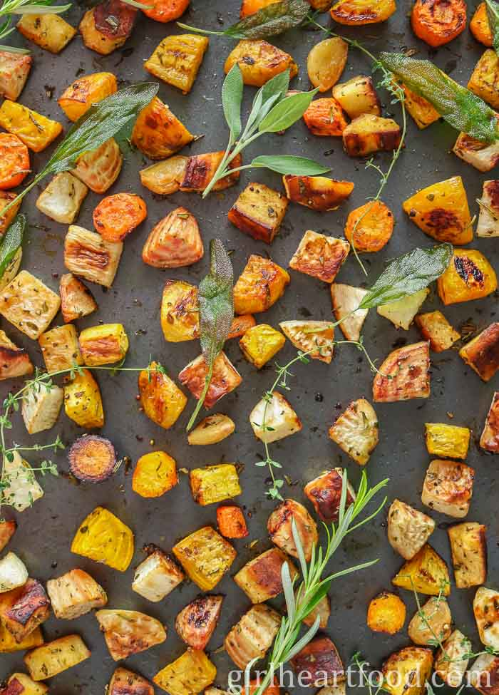 Sheet pan of roasted vegetables with herbs.