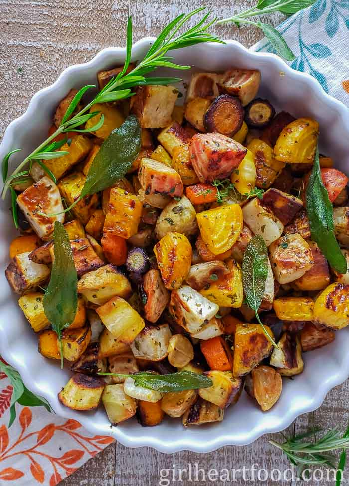 White round dish with roasted root veg and garnished with herbs.