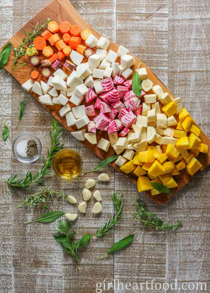 Ingredients for a roasted root vegetables recipe with herbs and garlic on a wooden board.