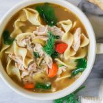 Bowl of a homemade chicken noodle soup recipe garnished with fresh dill.