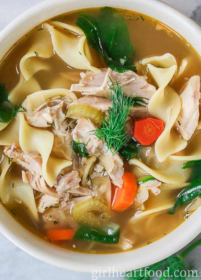 Bowl of the best homemade chicken noodle soup with dill garnish.