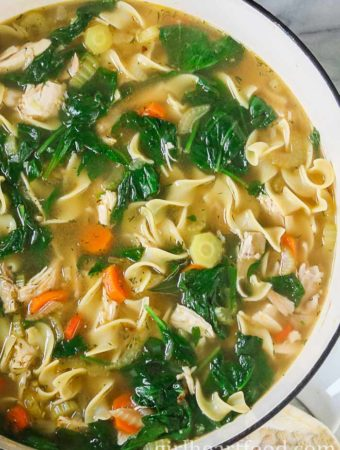 Large pot of the best homemade chicken noodle soup with egg noodles, spinach and carrots.