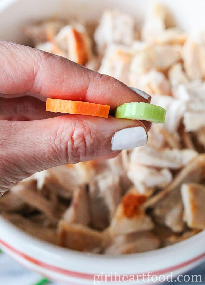 Holding up a piece of chopped carrot and celery to go in a homemade chicken noodle soup recipe.