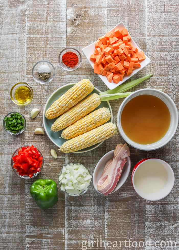 Ingredients for a sweet corn soup with cream and bacon on a wooden board.