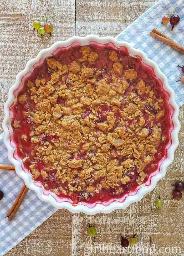 Round pie dish of homemade gooseberry crumble on a blue and white checkered cloth.