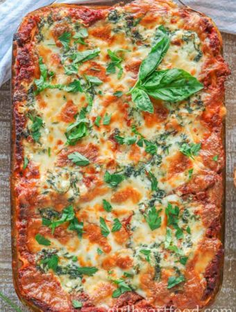 Casserole dish of homemade lasagna garnished with fresh basil and parsley.