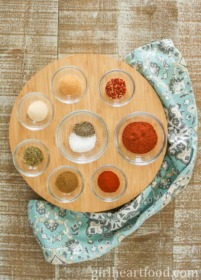 Ingredients for an easy taco seasoning recipe in glass dishes on a round wooden board.