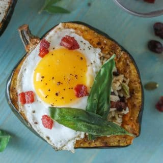 Roasted acorn squash stuffed with rice and topped with a fried egg, crispy bacon and sage leaves.