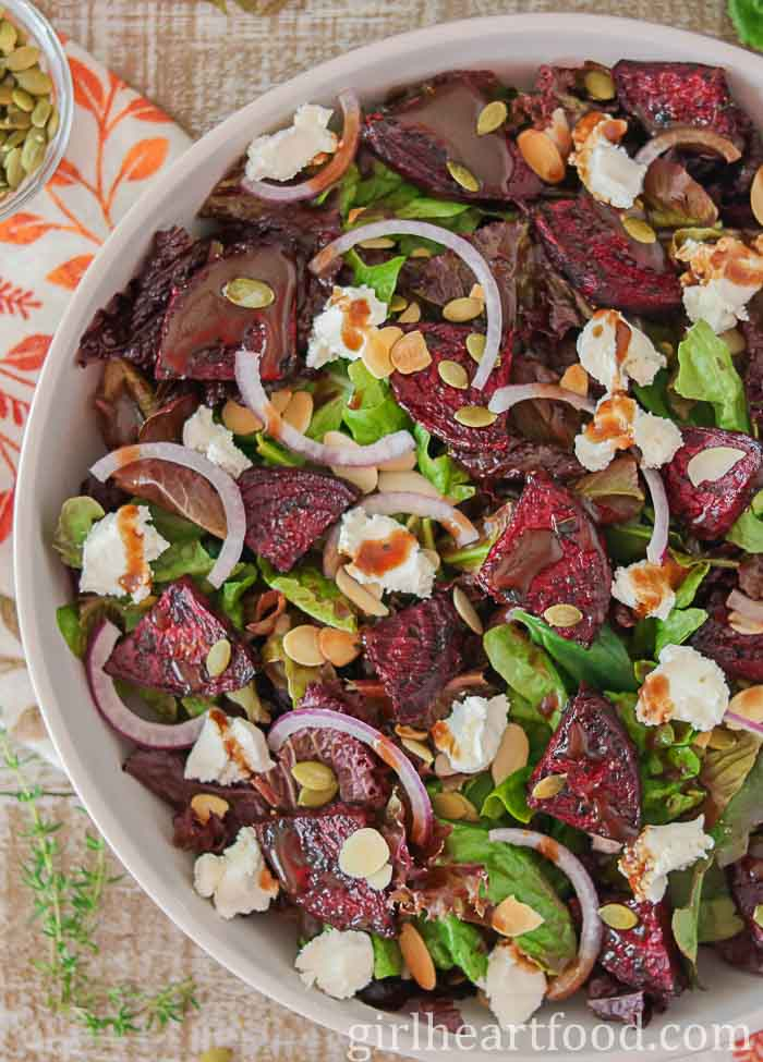 Large dish of a roasted beet salad with goat cheese, red onion, almonds and pumpkin seeds.