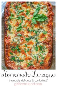 Pan of cheesy meat lasagna garnished with fresh basil and parsley.