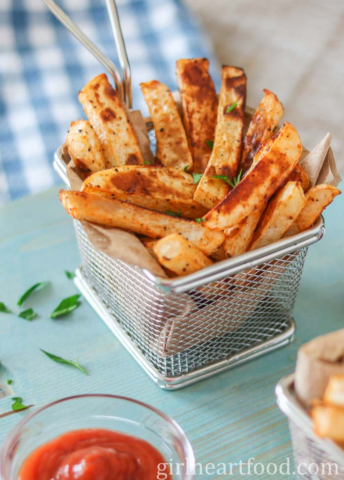 Stainless steel basked of oven-baked turnip fries garnished with parsley and alongside dish of ketchup.