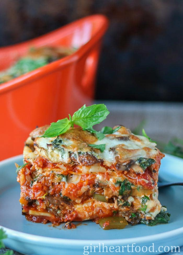 Large piece of vegetarian lasagna garnished with fresh basil on a blue plate.