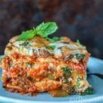 Large piece of roasted vegetable lasagna garnished with fresh basil on a blue plate.