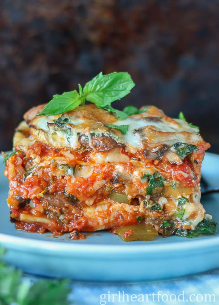 Large piece of veggie lasagna garnished with fresh basil on a blue plate.
