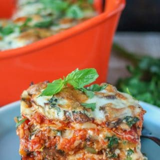 Large piece of meatless lasagna garnished with fresh basil on a blue plate.