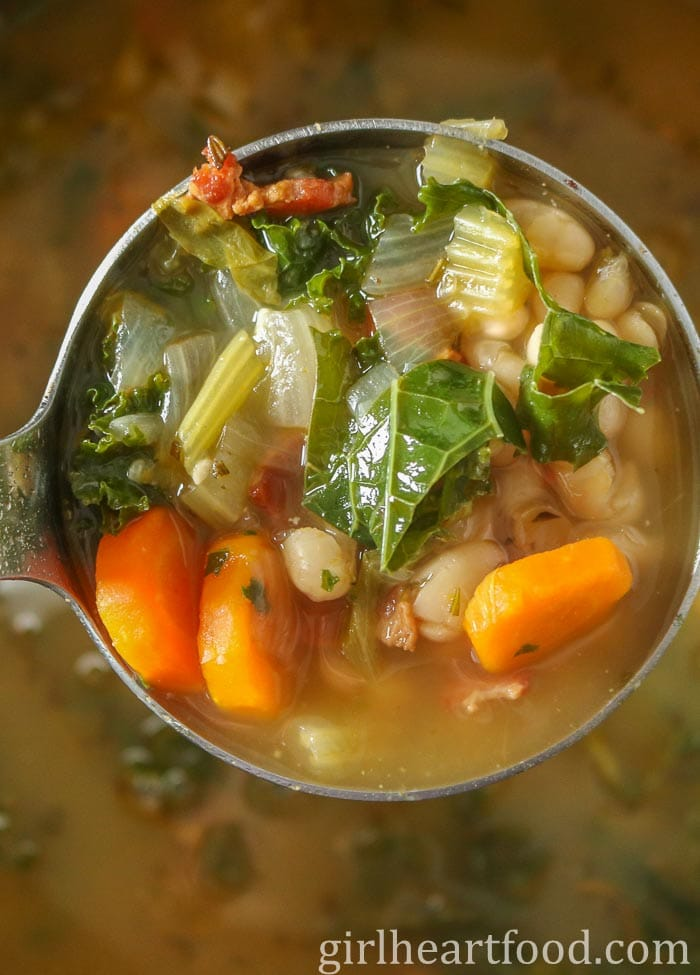 Ladle of bacon and bean soup with vegetables.