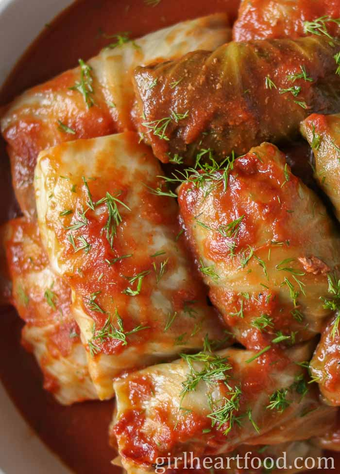 Stuffed cabbage rolls with tomato sauce and dill garnish.