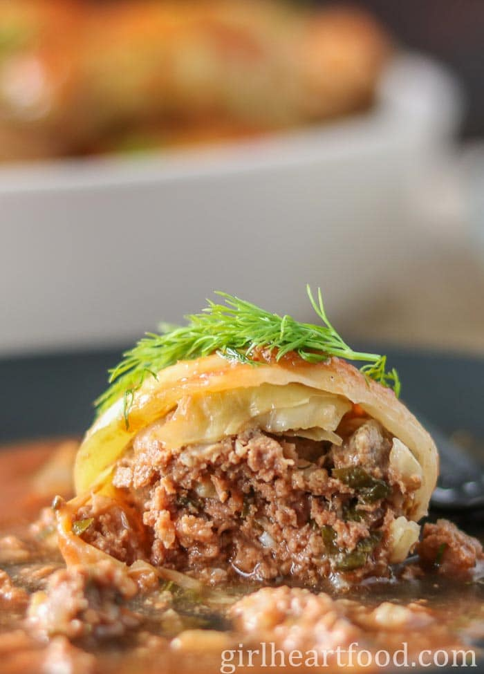 A stuffed cabbage roll on a plate that has been cut to show interior.
