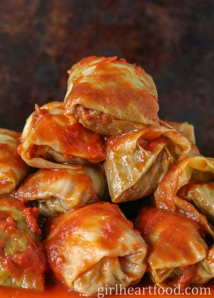 Old fashioned cabbage rolls piled high with tomato sauce over them.