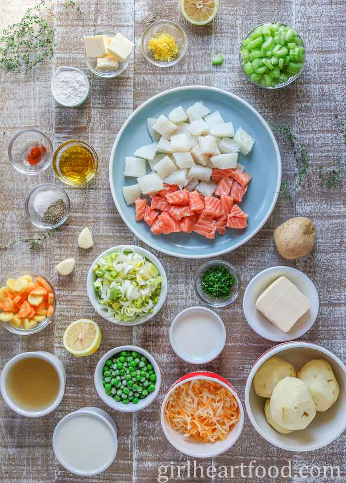 Ingredients for the best fish pie recipe on a wooden board.