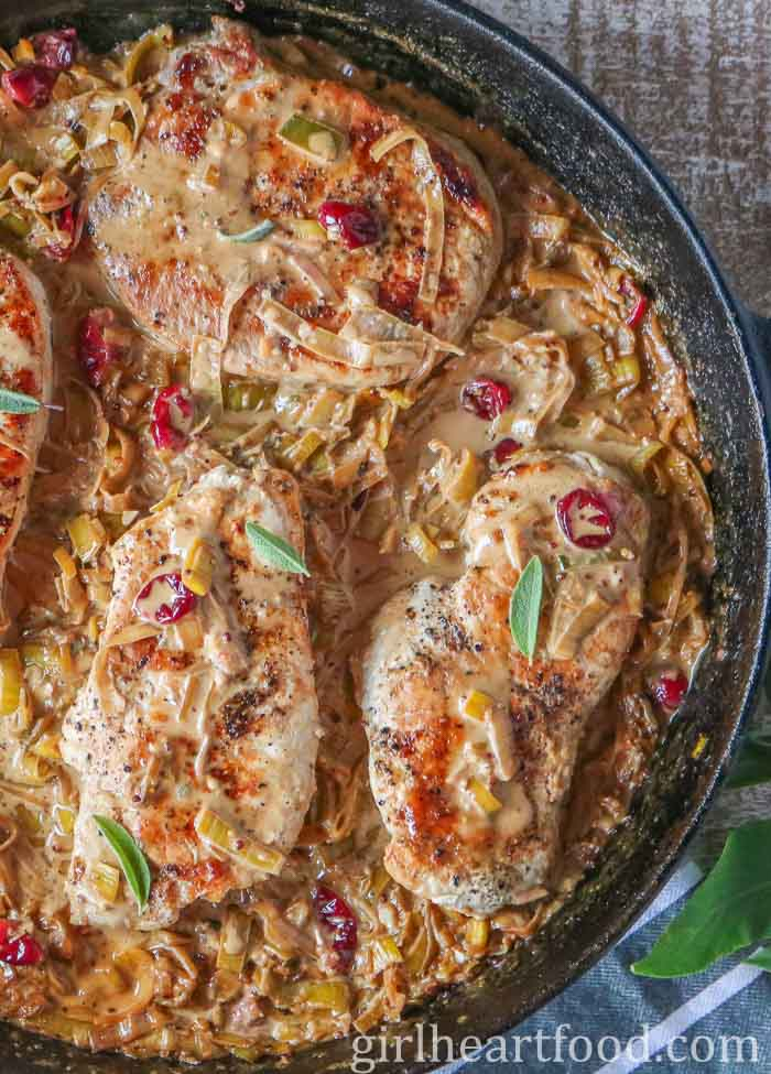 Skillet of fried boneless pork chops with a creamy mustard sauce and fresh sage.