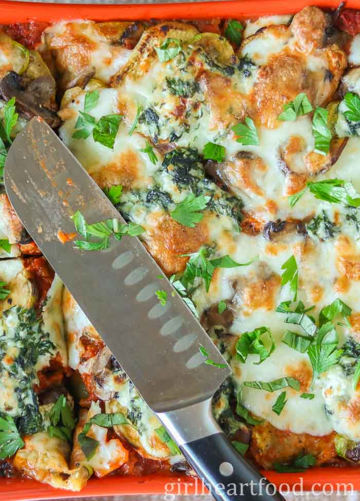 Pan of roasted vegetable lasagna garnished with fresh basil and with a knife on top.