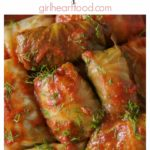 Dish of stuffed cabbage rolls with tomato sauce and fresh dill garnish.