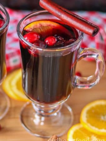 Mug of slow cooker mulled wine garnished with orange, cranberries, star anise and a cinnamon stick.