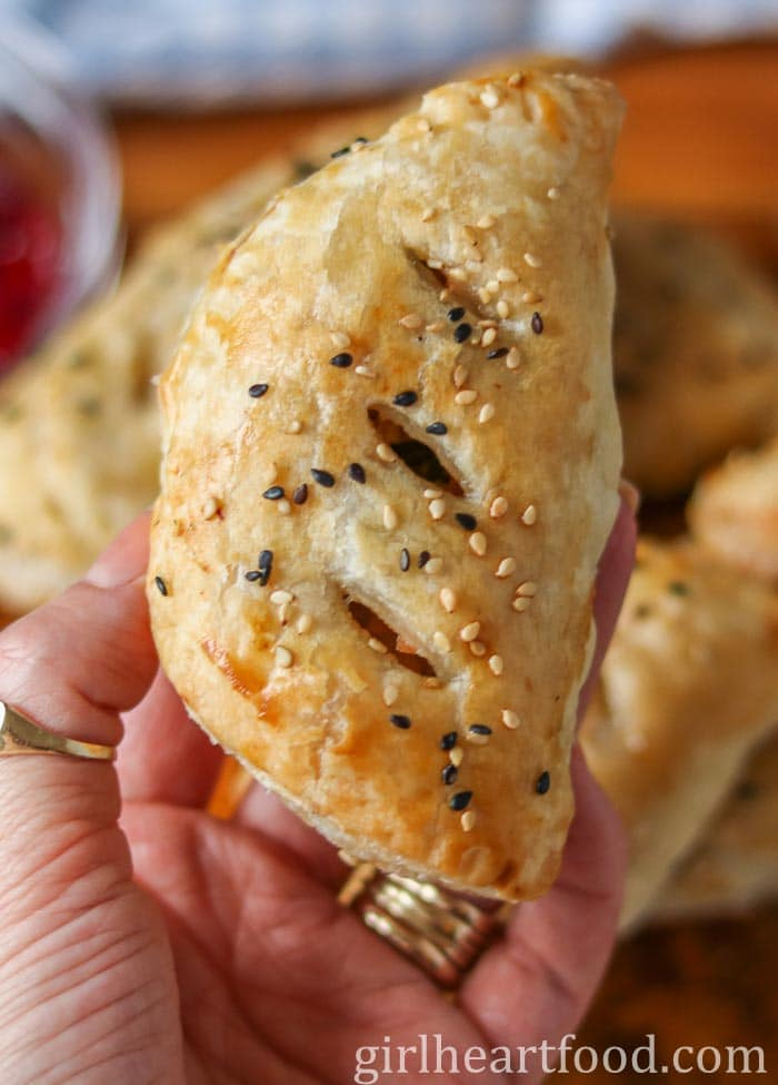 Someone holding up a meat hand pie sprinkled with sesame seeds.