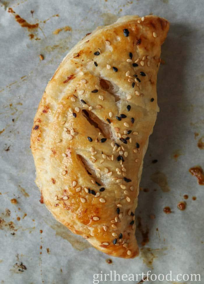 A savory hand pie sprinkled with sesame seeds.