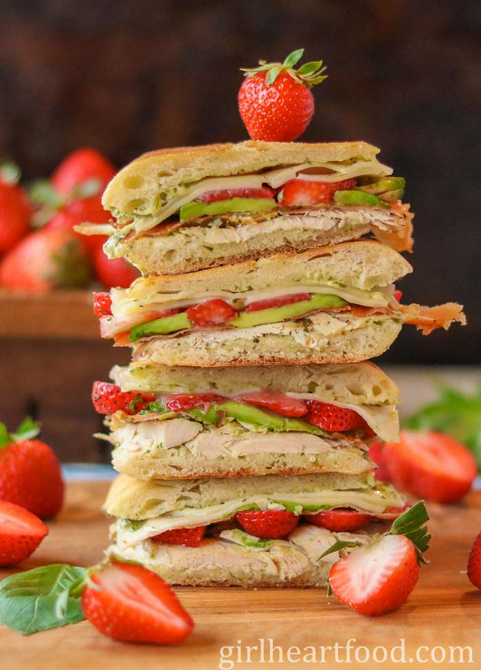 Two cut leftover turkey sandwiches stacked on top of each other alongside some strawberries.