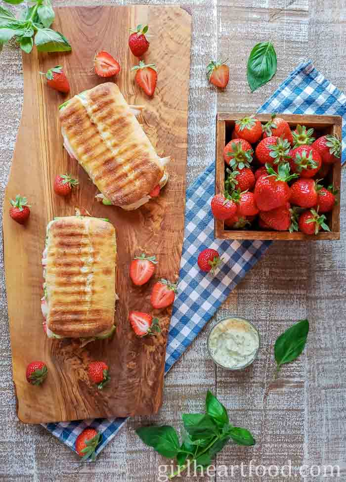 Two panini sandwiches on a wooden board alongside some strawberries and basil.