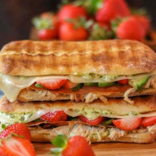 Two turkey panini sandwiches stacked on top of each other alongside some strawberries.