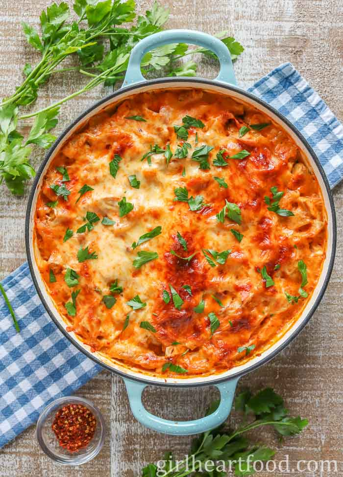 Large round dish of cheesy turkey pasta bake garnished with fresh parsley.