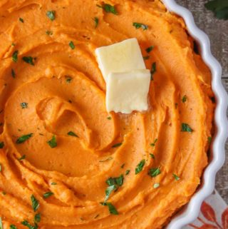 Large white dish of whipped sweet potatoes garnished with parsley and butter.