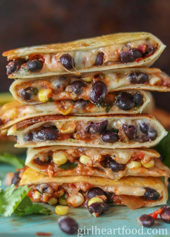 Tall stack of black bean quesadillas on a blue board.