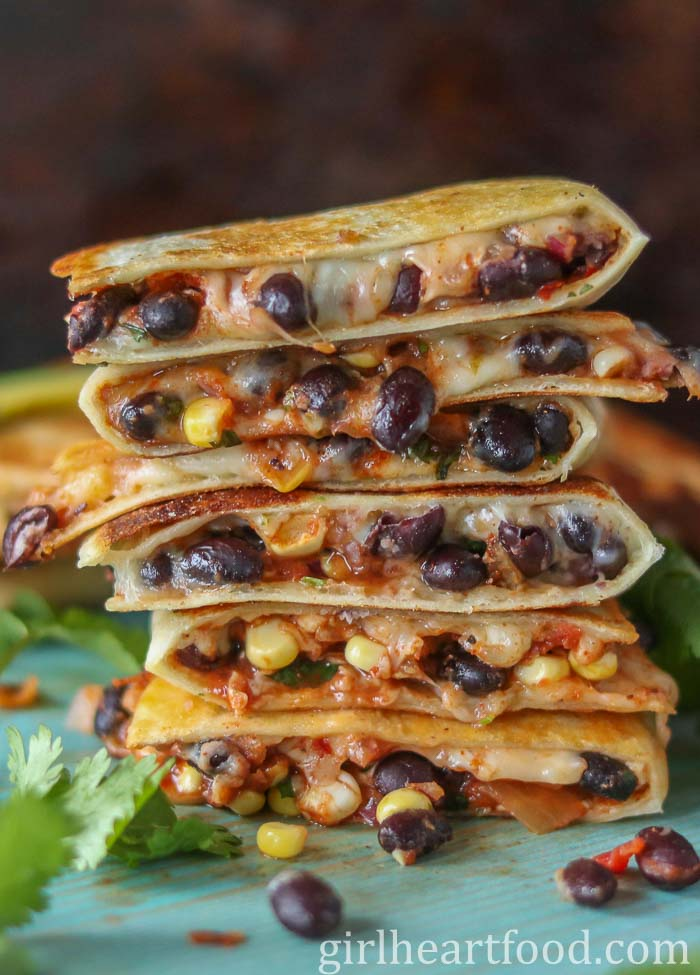 Tall stack of cheesy black bean quesadillas on a blue board.