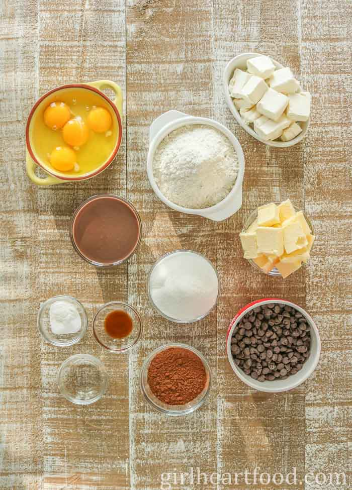 Ingredients for chocolate bundt cake on a wooden board.