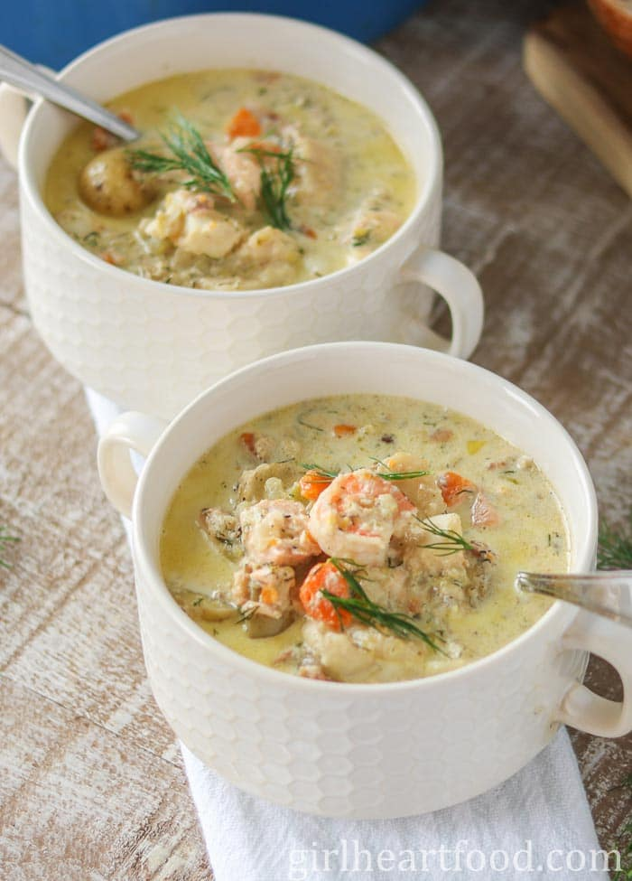 Two bowl of creamy fish chowder with dill on top.