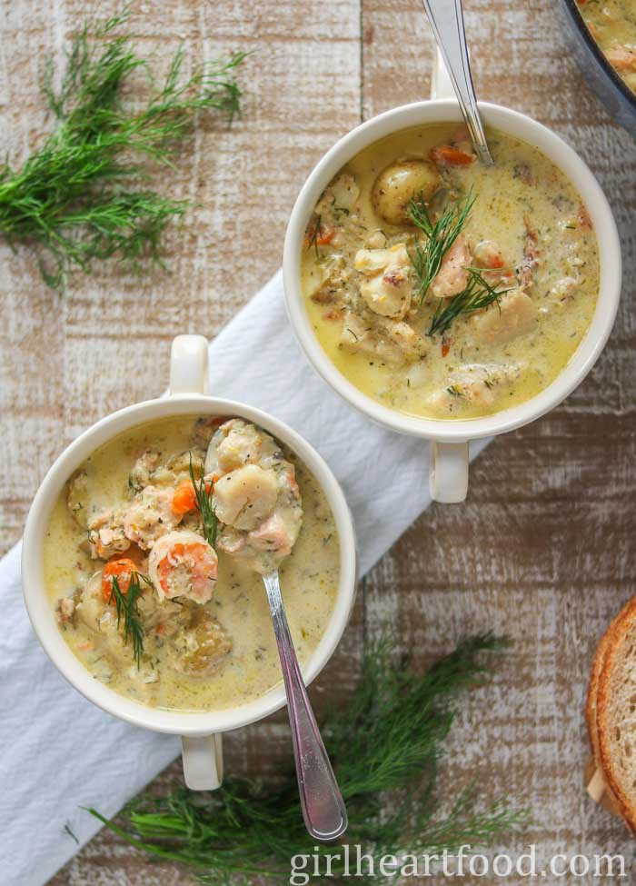 Two bowls of seafood chowder garnished with fresh dill and next to some dill.