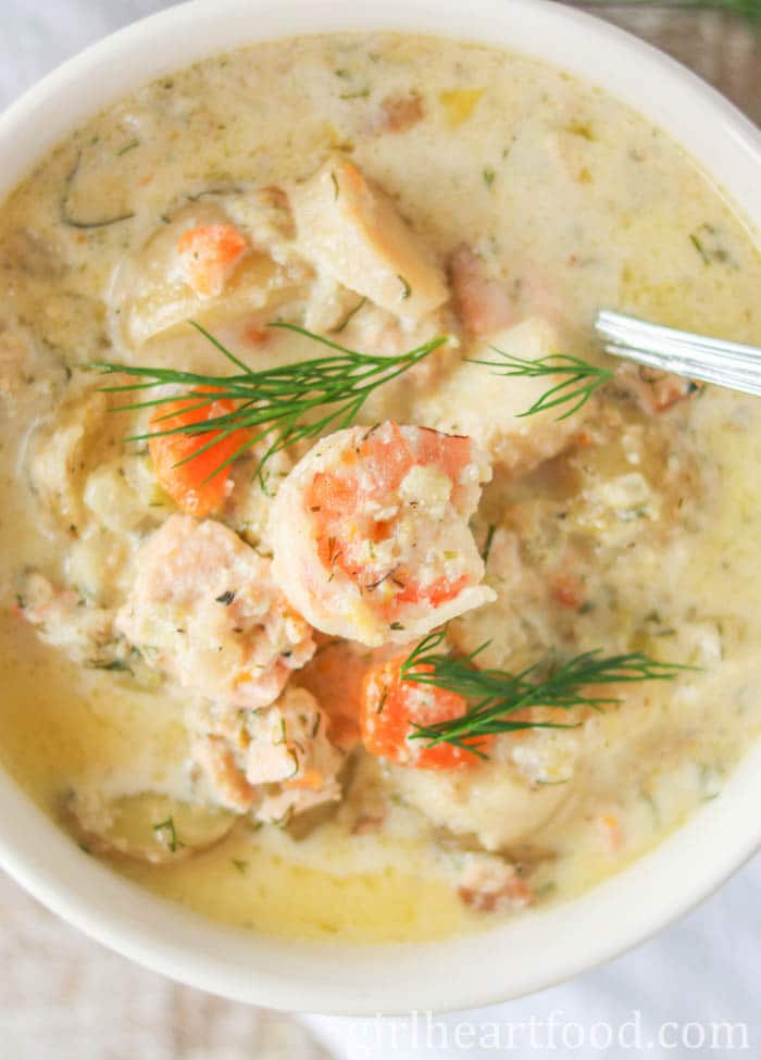 Close-up of a bowl of seafood chowder with dill on top.