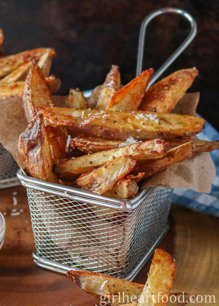 Stainless steel basket of crispy potato wedges.