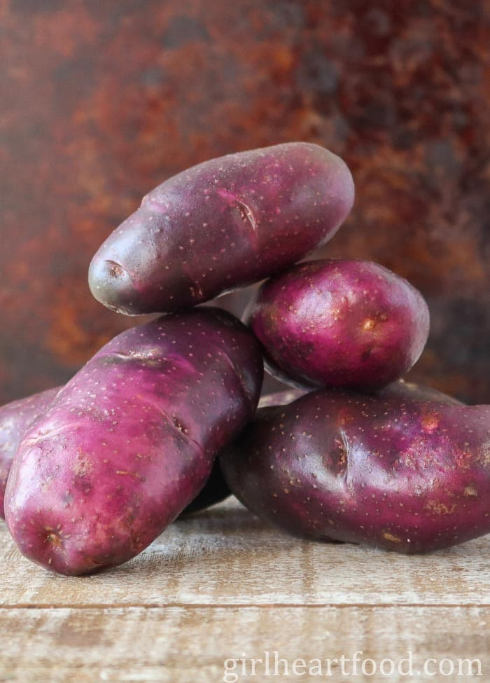 Stack of purple potatoes on a wooden board.