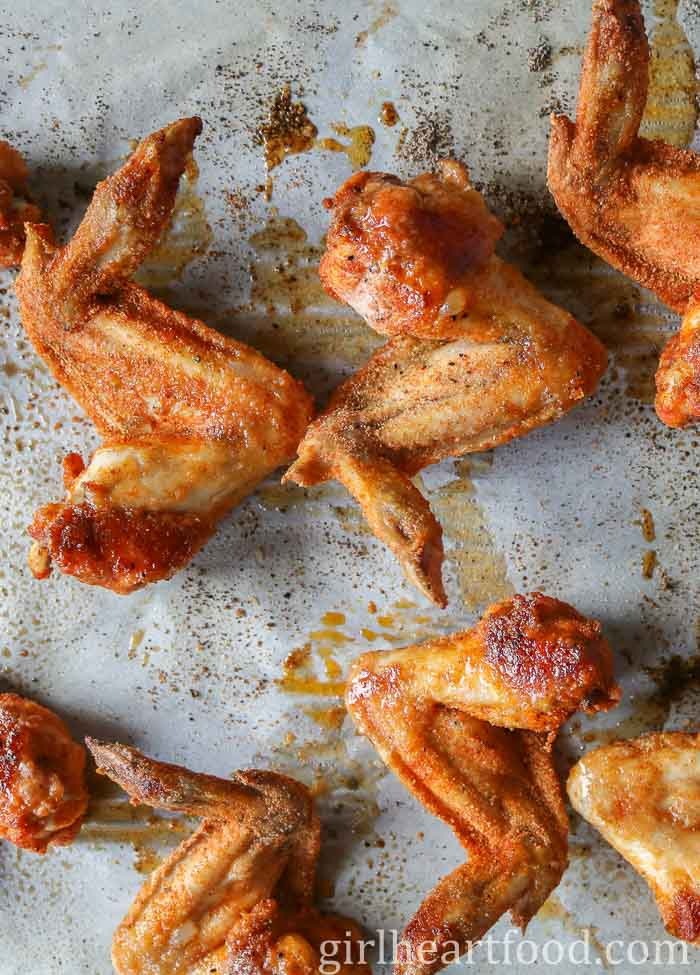 The underside of partially cooked chicken wings on a parchment paper lined sheet pan.