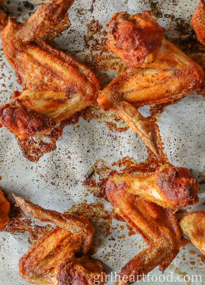Crispy baked wings on a parchment paper lined baking sheet after coming out of the oven.